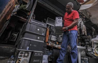 Juan Carlos Araujo muestra uno de los aparatos tecnológicos que a diario repara en un módulo ubicado en la esquina de la calle 29 con carrera 39 de El Boliche.