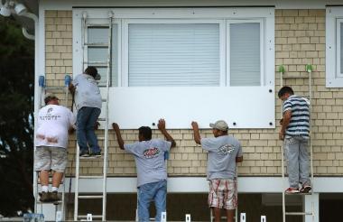 Residentes en Viginia del Norte protegen la fachada de su vivienda ante la cercanía del paso del huracán Florence.