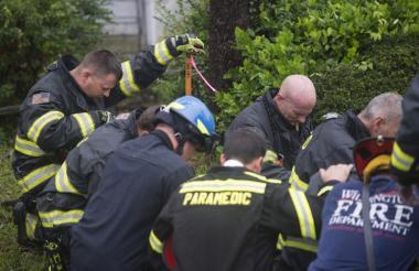 Bomberos durante las operaciones de remoción del árbol que cayó en la vivienda.