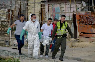 Policías y funcionarios cargan una camilla metálica con un cadáver.