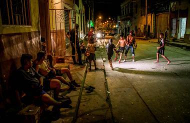 Adolescentes y adultos juegan fútbol en una cancha improvisada en la calle 34 con carrera 38, apenas son las 10:00 de la noche.
