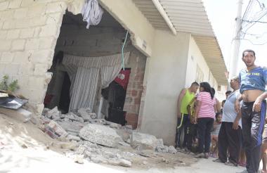 Personas observan la vivienda donde chocó la van que ocasionó la tragedia.