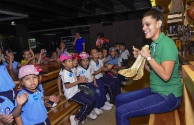 Alexandra Niebles, guía del museo, le muestra a los niños el particular sonido de la charrasca.
