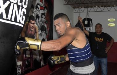 El púgil barranquillero Álex Therán golpea el saco mientras su entrenador Miguel Guzmán lo observa.