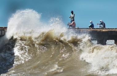 Las olas en la playa de Puerto Colombia golpean la vieja estructura del muelle.