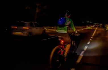 Un ciclista es iluminado por la luz de un vehículo mientras transita por la vía.