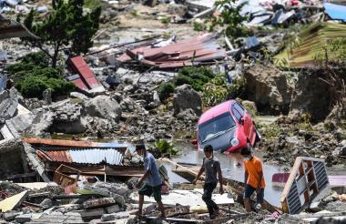 Algunas personas caminan por encima de los escombros.
