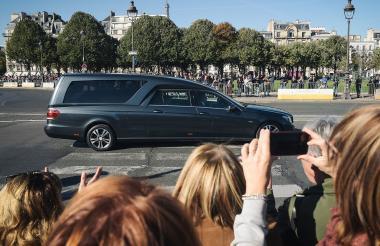 Personas viendo el coche fúnebre que lleva el ataúd del cantante.