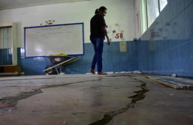 Una docente muestra el estado en el que está el salón de clases, cuyo suelo se encuentra agrietado.