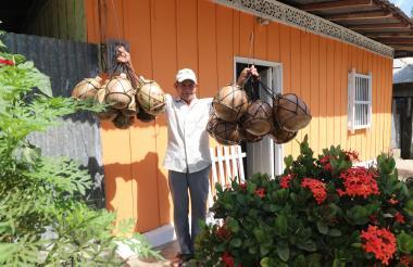 Felipe Santiago Month Ramírez enseña algunas de las cosas que fabrica, como calabazos, en la entrada de su casa en Sincé.