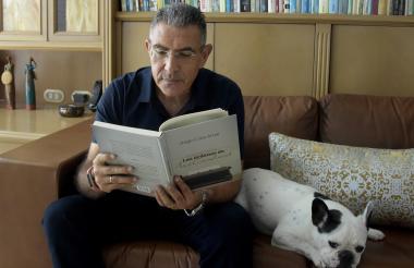 Jorge Cura lee un aparte de su libro 'Las órdenes de McCausland' en la sala de su apartamento, en Barranquilla, junto a su perro Baltazar.