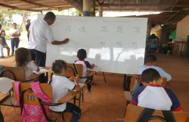 El profesor explica ante los pequeños alumnos. Al fondo está la mesa de billar.