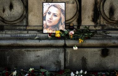 Flores frente al retrato de la periodista.