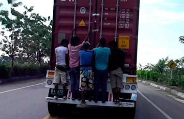Menores colgados de un camión.