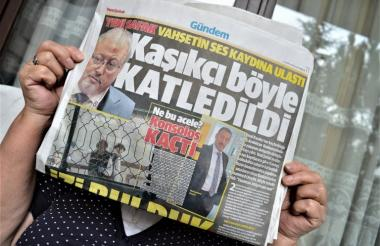 """Una mujer sostiene Yeni Safak, un diario turco oficia que titula:  """"Así es como Khashoggi fue asesinado"""" con una foto periodista asesinado y el cónsul general de Arabia Saudita en Estambul, Mohammad al-Otaibi."""