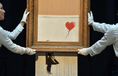 Empleados de Sotheby's junto a la obra de Banksy, hoy titulada 'Love is in the bin'.