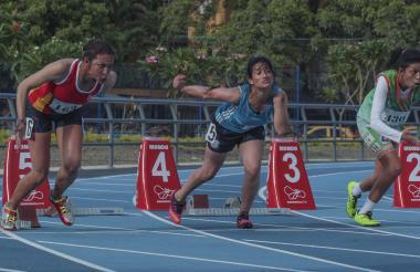 Atletas corriendo los 100 metros planos en el estadio de Atletismo.
