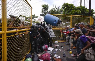 La Policía antidisturbios de Guatemala se enfrenta a migrantes hondureños que intentan cruzar el puente fronterizo Guatemala-México en Ciudad Tecún.