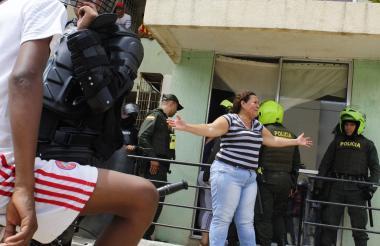 Una mujer reclama a algunos agentes por el desalojo.