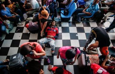 Varios venezolanos descansan en la terminal de transporte de la ciudad peruana de Tumbes.