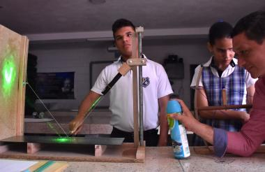Los alumnos Elian García y Charlotte George, junto al docente  José Camargo en clase de Física.