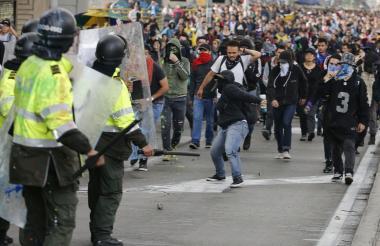 Un grupo de manifestantes enfrenta a un piquete de la Policía, en una calle de Bogotá, el pasado jueves.