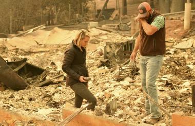 Chris y Nancy Brown inspeccionan los restos de su residencia quemada por el voraz incendio.