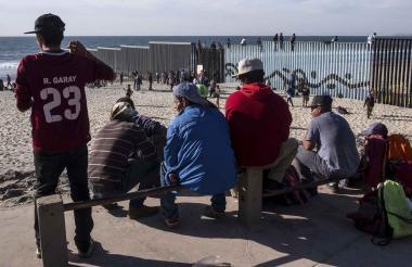 Algunos centroamericanos esperan la llegada de otros caminantes, mientras  toman un descanso en la playa del estado de Tijuana.