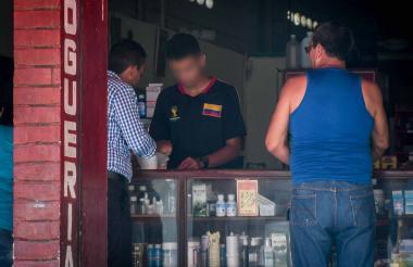 El hombre vestido de negro entrega un tarro blanco de cianuro de potasio mientras otro comprador observa.
