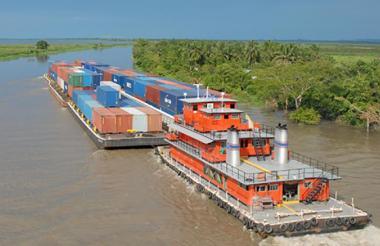 Un convoy transporta una carga de contenedores por el río Magdalena.