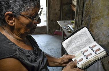 """Josefa Constante enseña unas fotos de su hijo, Deivis Crespo, que asegura tener guardadas dentro de una biblia para """"que Dios siempre lo cuide""""."""