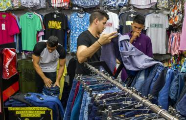 Vendedores en el Centro de Barranquilla realizan una negociación con el cliente para que compre la ropa que está siendo mostrada.