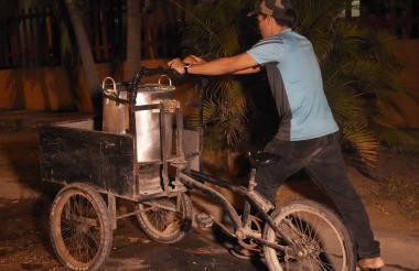 Ender Hurtado camina junto a su triciclo y la olla de peto por una calle oscura del norte de Barranquilla, para regresar a su casa.