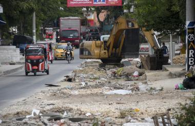La calle se encuentra con escombros y con maquinaria pesada detenida.