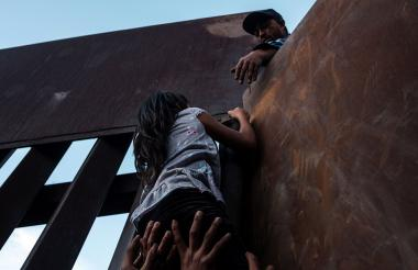 Niña intenta pasar el muro en México.