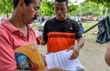 Juan Castañeda (izq.) muestra los documentos que usó para tramitar el PEP.