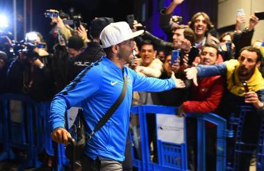 Carlos Tevez saluda a los aficionados de Boca a su llegada a Madrid.