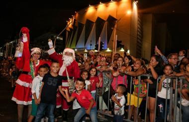 Asistentes se toman fotografías junto a Santa.