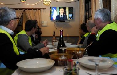 """""""Chalecos amarillos"""" observan la alocución del presidente Macron."""