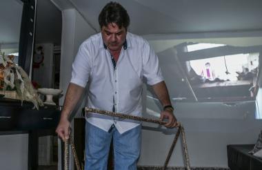 Uno de los vecinos muestra las varillas de hierro que han caído en su vivienda.