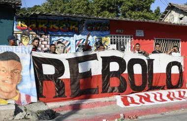 Integrantes de la barra Frente Rojiblanco Sur posan con sus trapos en una de las calles del barrio Rebolo, suroriente de Barranquilla.