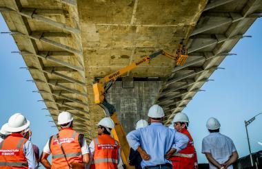 Los ingenieros del proyecto observan las reparaciones al nuevo puente.