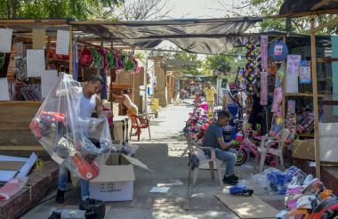 Algunos vendedores organizan la mercancía en los puestos del Universal.