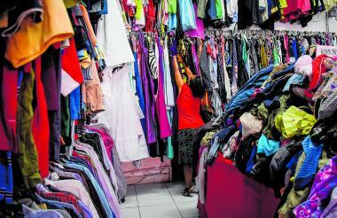 Una mujer busca entre la ropa colgada en uno de los establecimientos que se dedican a comercializar ropa de segunda mano, en el centro de Barranquilla.