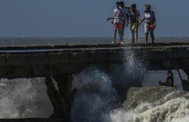 Un grupo de personas camina sobre la superficie de lo que queda del Muelle de Puerto Colombia.