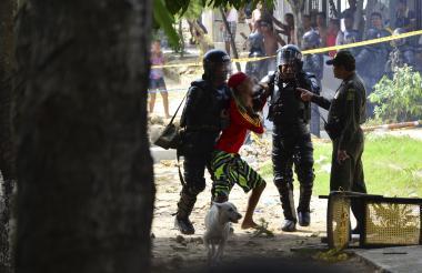 Policías y miembros del Esmad atienden una riña en un barrio popular mientras la comunidad observa la acción.