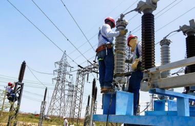 Trabajadores del sector eléctrico haciendo mantenimiento a torres de energía.