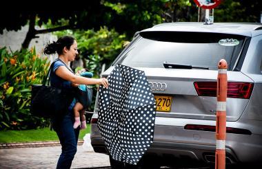 Una mujer con su bebé en brazos intenta sostener el paraguas mientras la brisa arrecia contra él.