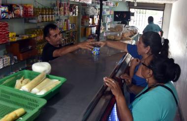 Un tendero el La Ciudadela 20 de julio atiende a un grupo de clientes.