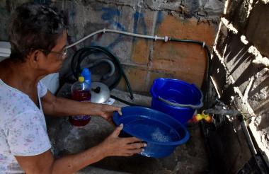 Una vecina del barrio Buenos Aires almacenando agua.